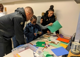 Two student volunteers with JMU CMSS help children cut out and make paper people