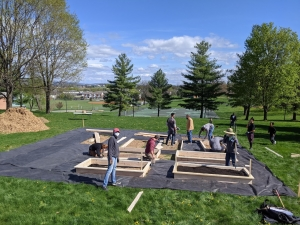 Volunteers build garden boxes, fill boxes with soil, and help with the Kelley Street garden April 17 during community build day