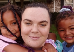 FSS Graduate Amber with her two girls on either side in front of their new home.