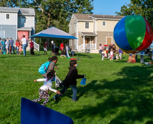 Children chase a large beach ball in the foreground as families mingle with community partners in the back.