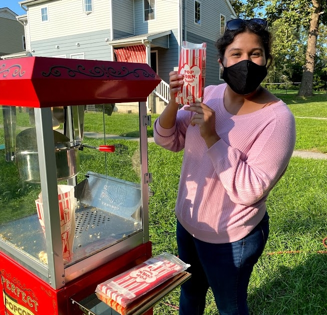 Heidi with Harrisonburg Baptist poses with a bag of popcorn next to a red popcorn machine.