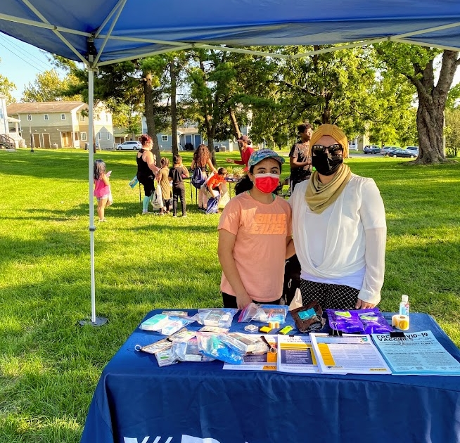 An employee with the Virginia Department of Health and a young girl stand side by side at the VDH table under a canopy.