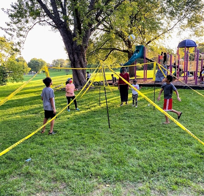 Kids stand on four corners of a 5ft high 4-square volleyball net.